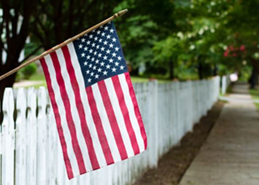 American flag in front of a white fence